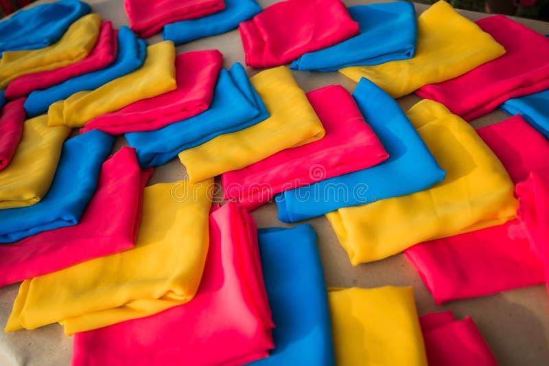 Pila di vestiti variopinti o di sciarpe, sulla tavola di legno fotografia stock libera da diritti