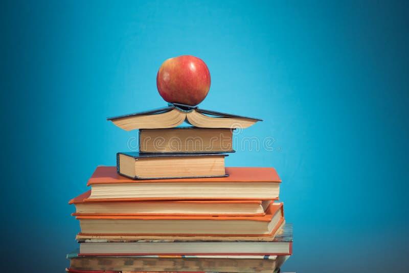 Pila e mela di libro sul fondo blu di istruzione, di nuovo al concetto della scuola immagini stock