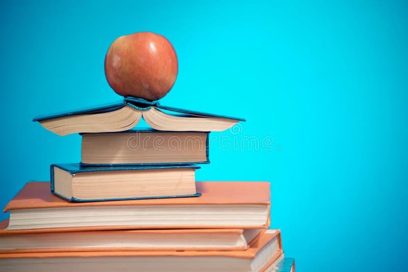 Pila e mela di libro sul fondo blu di istruzione, di nuovo al concetto della scuola fotografia stock