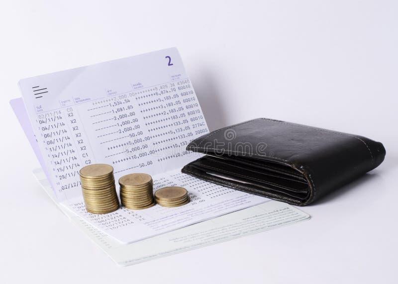 Pila e tasca delle monete dei soldi sul concetto di prestito di risparmio della banca del libro immagini stock libere da diritti
