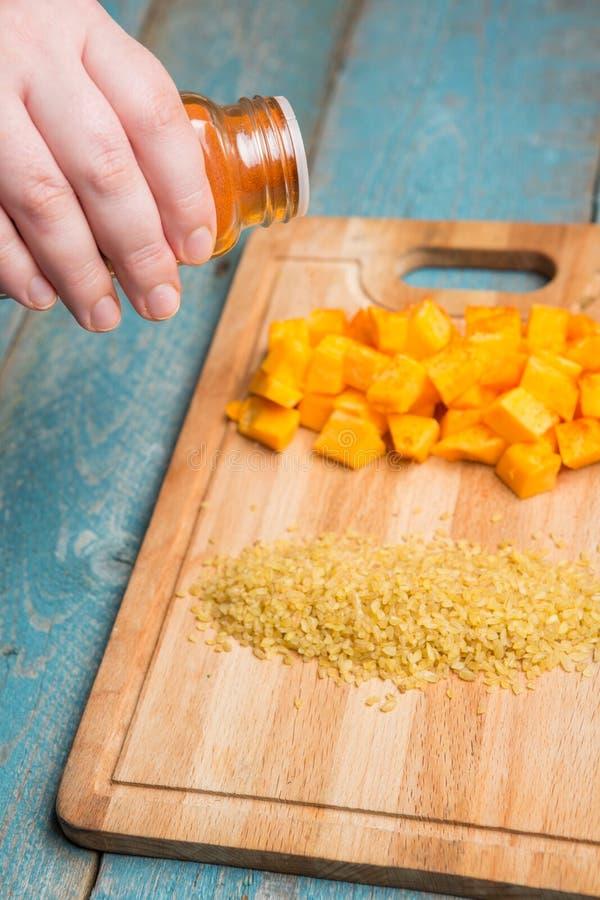 Pila femenina del condimento de la mano de bulgur seco del trigo foto de archivo