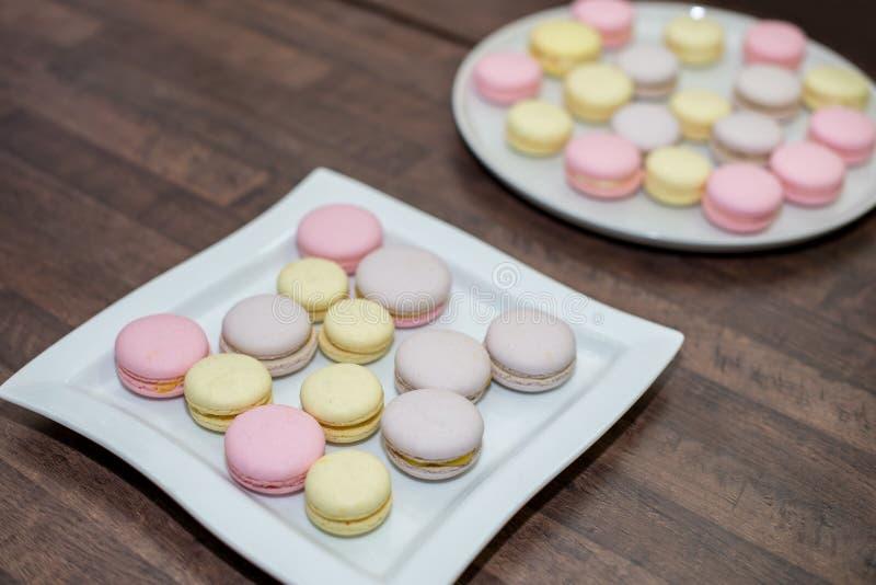 Pila francesa o italiana colorida de los macarons en la placa blanca puesta en la tabla de madera con el espacio de la copia para imagenes de archivo