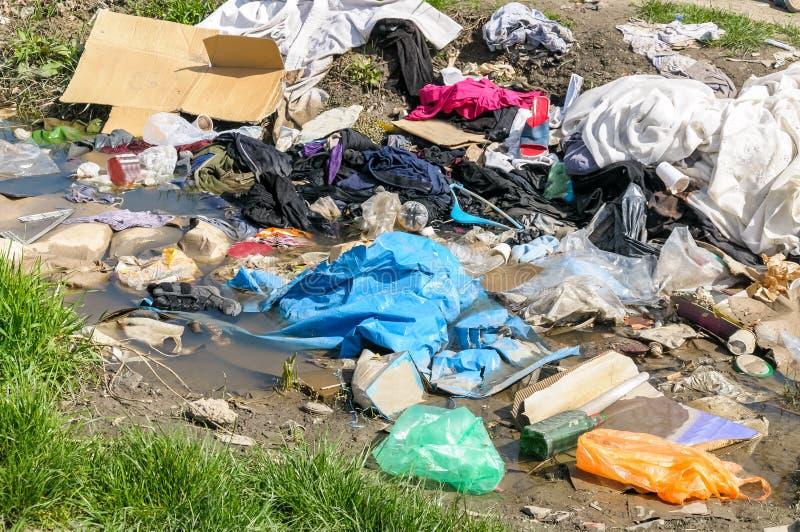 Pila grande de basura y de desperdicios en el agua de río que contamina la naturaleza con la litera fotos de archivo