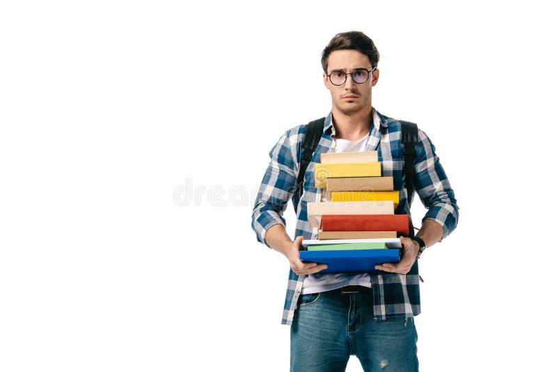 pila hermosa triste de la tenencia del estudiante de libros y de mirar la cámara fotos de archivo