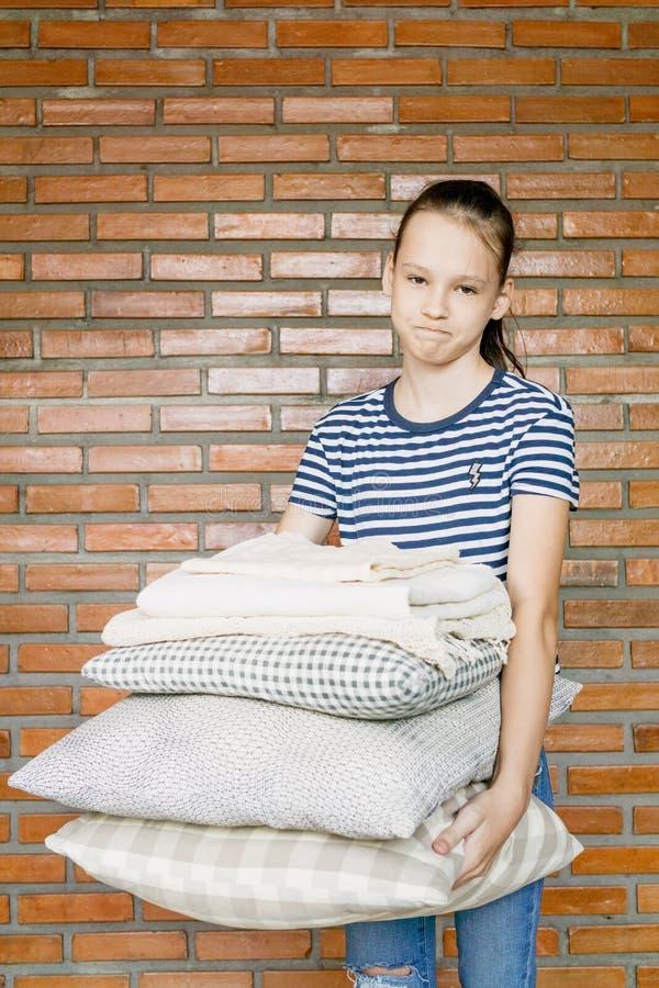 Pila infelice della tenuta della ragazza del preteen di cuscini e di coperte contro il mattone wal Compito, pulente fotografia stock