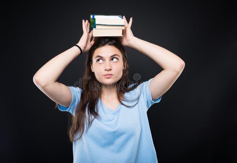 Pila joven de la tenencia del estudiante universitario de libros en la cabeza fotos de archivo libres de regalías