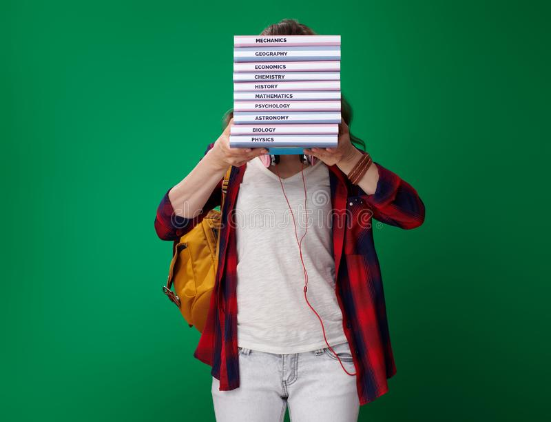 Pila joven de la tenencia de la mujer del estudiante de libros delante de la cara fotografía de archivo libre de regalías