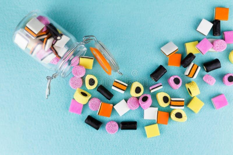 Pila juguetona, colorida de regaliz allsorts del caramelo que desborda el tarro imagen de archivo libre de regalías