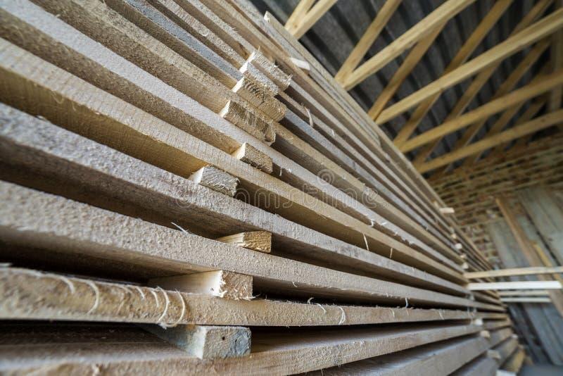 Pila larga cuidadosamente llenada de tableros de madera dentro del sitio del ático bajo construcción fotos de archivo libres de regalías