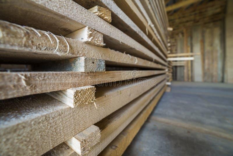 Pila larga cuidadosamente llenada de tableros de madera dentro del sitio del ático bajo construcción fotos de archivo