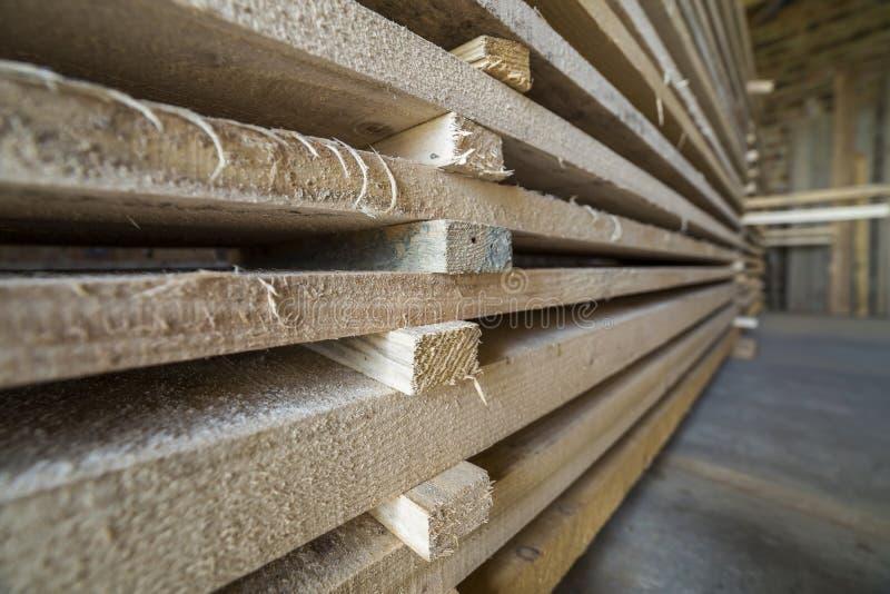 Pila larga cuidadosamente llenada de tableros de madera dentro del sitio del ático bajo construcción foto de archivo