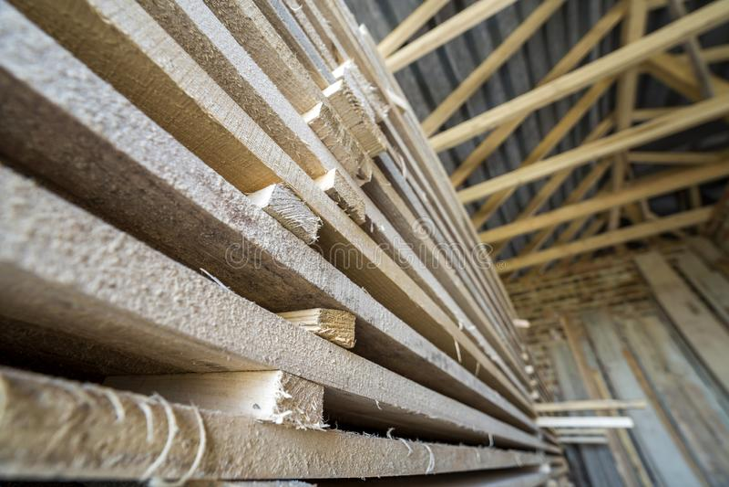 Pila larga cuidadosamente llenada de tableros de madera dentro del sitio del ático bajo construcción fotografía de archivo