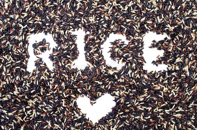 Pila mezclada de arroz negro y de arroz blanco con palabra y forma del arroz fotos de archivo
