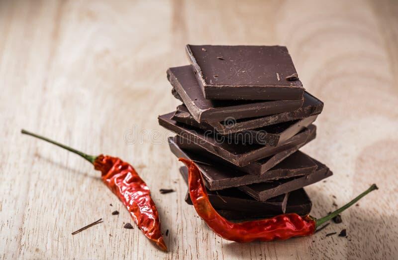 Pila oscura de las barras de chocolate con Chili Peppers en la tabla de madera imágenes de archivo libres de regalías