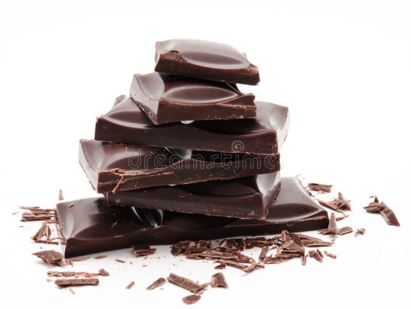 Pila oscura de las barras de chocolate con las migas aisladas en un blanco imagen de archivo