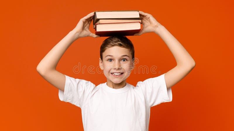 Pila positiva de la tenencia del colegial de libros en su cabeza fotos de archivo