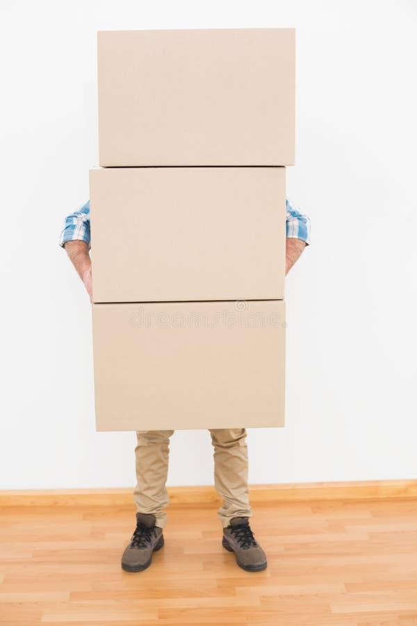 Pila que lleva del hombre de cajas móviles de la cartulina imágenes de archivo libres de regalías