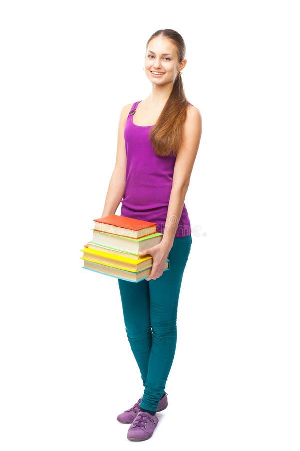 Pila sonriente feliz de la tenencia de la muchacha del estudiante de libros fotografía de archivo libre de regalías