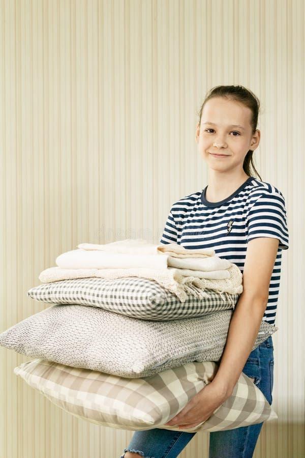 Pila sorridente della tenuta della ragazza del preteen di cuscini e di coperte Compito, tessuto domestico fotografia stock