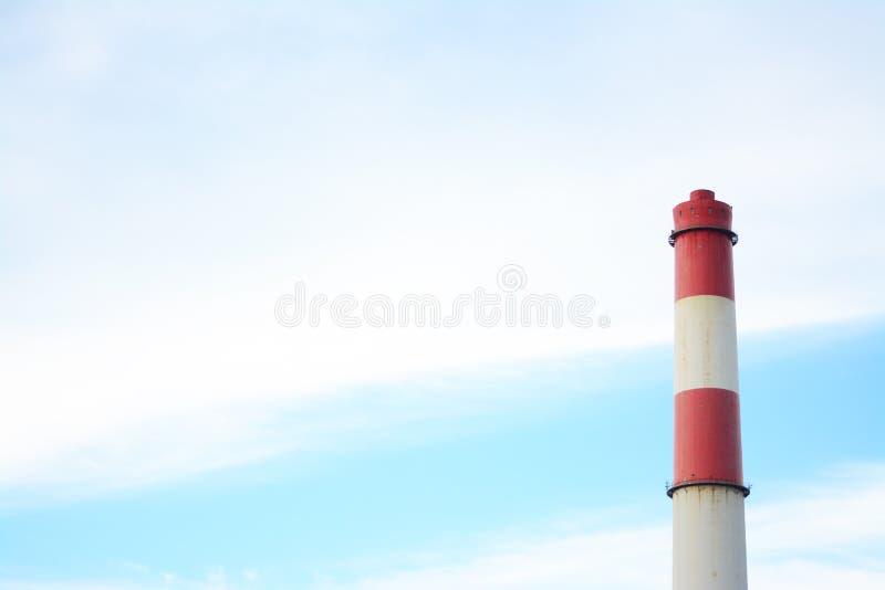 Pila verticale bianca e rossa del gas di combustione del tubo di centrale elettrica con il fondo del cielo blu immagini stock libere da diritti