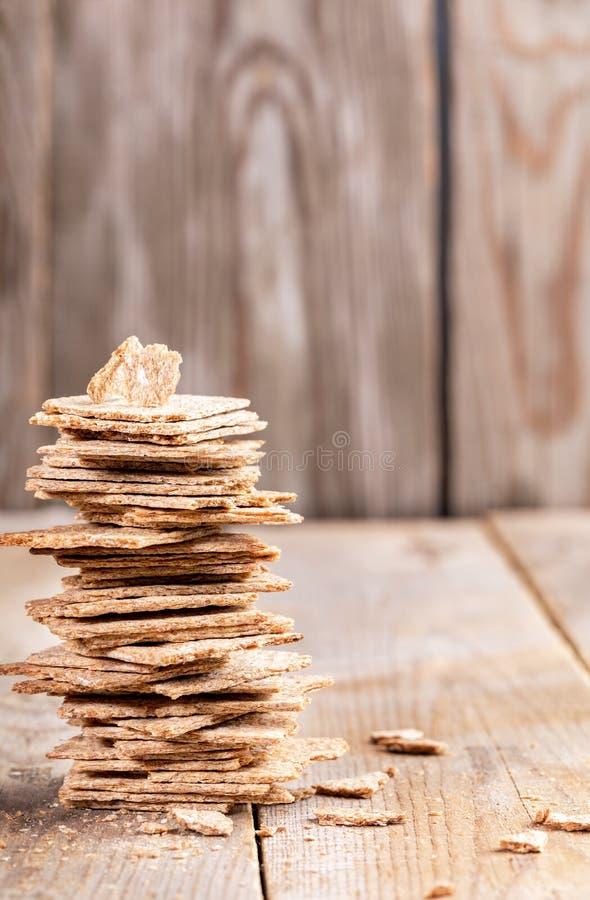 Pila verticale di pezzi rotti di pani croccanti del cereale su fondo di legno fotografia stock libera da diritti