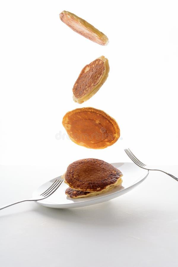 Pila volante di pancake con il mirtillo, la mora ed il lampone isolati su fondo bianco fotografia stock libera da diritti