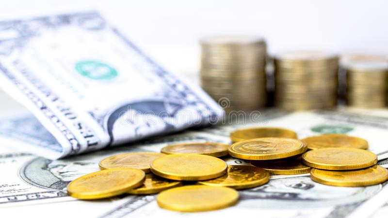 Pila y dólar de oro de las monedas billete de banco en el backgro blanco de la tabla fotografía de archivo libre de regalías