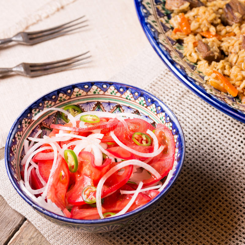 Pilaf and achichuk salad in handmade plate on wooden background stock images