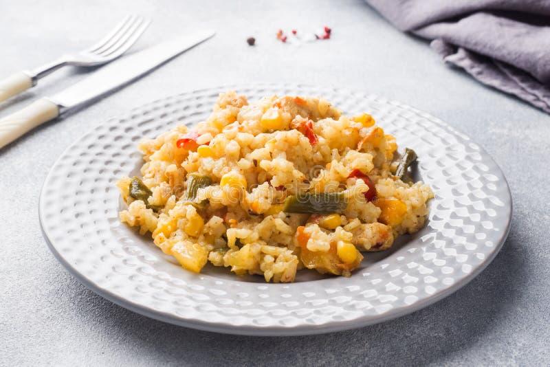Pilaf avec légumes et poulet dans une assiette grise sur fond gris photographie stock