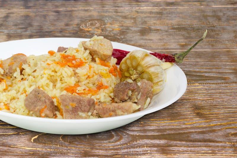 Pilaf cocinado en el plato blanco en el primer rústico de la tabla foto de archivo
