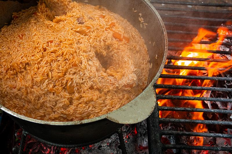 Pilaf cooking on fire outdoor. Open air kitchen at party picnic. Big pot with dish of rice and meat stays on wire rack and steams. Close up image of meal dish stock photo