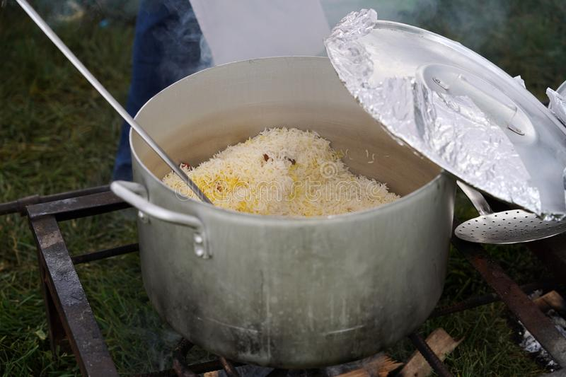 Pilaf cooking on fire outdoor. Open air kitchen at party. Open pot with rice and meat royalty free stock photography