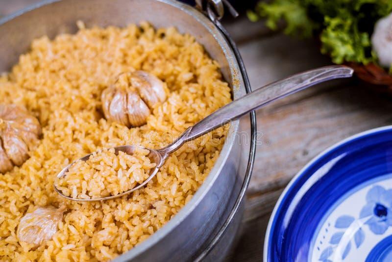 Pilaf del Uzbek, arroz con ajo en pote del hierro y placa fotografía de archivo libre de regalías