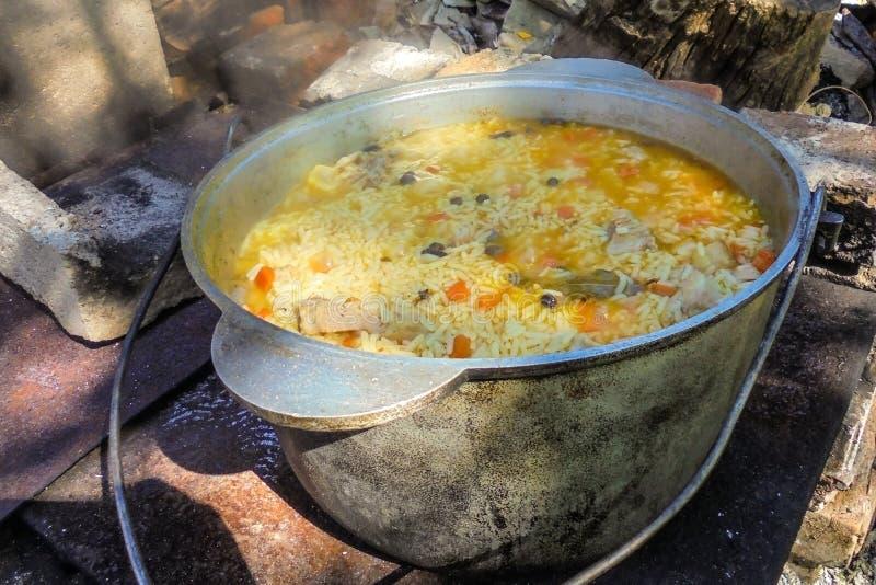 Pilaf gotuje w żeliwnym garnku na ogieniu zdjęcia stock