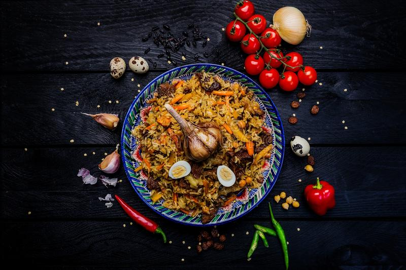 Pilaf and ingredients on plate with oriental ornament on a dark wooden background. Central-Asian cuisine - Plov Top view stock photo