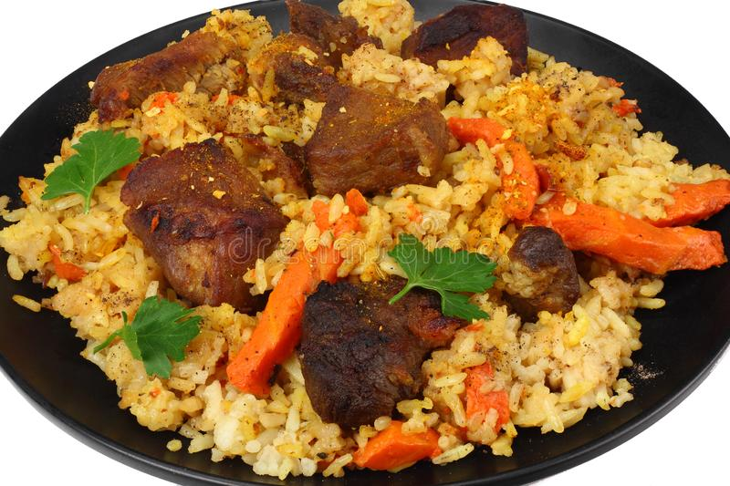 pilaf with meat on black plate isolated on white background royalty free stock image