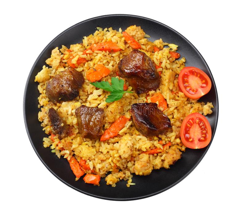 pilaf with meat on black plate isolated on white background. top view royalty free stock photography
