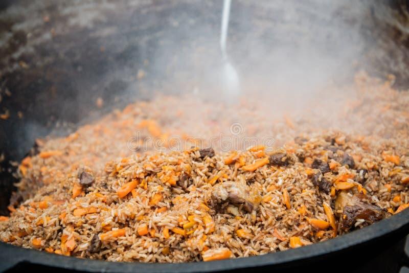 Pilaf saporito dell'Uzbeco in un calderone su fuoco all'aperto al festival dell'alimento della via immagine stock libera da diritti