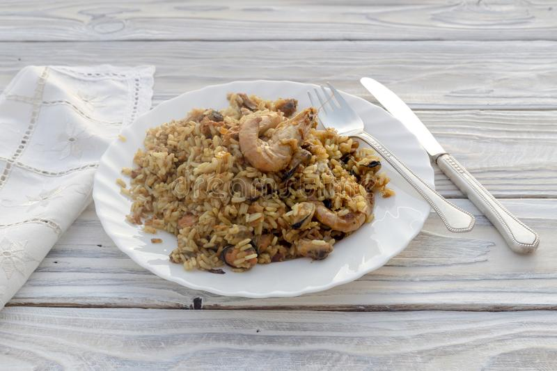 Pilaf from seafood Greek cuisine. Pilaf from seafood in a plate on a wooden table close-up Greek cuisine royalty free stock photography