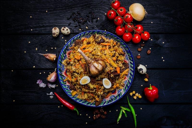 Pilaff och ingredienser på plattan med den orientaliska prydnaden på en mörk träbakgrund Central-asiat kokkonst - Plov bästa sikt arkivfoto