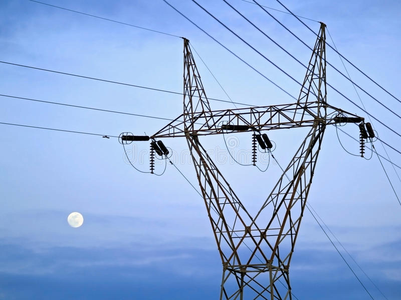 Pilar de la electricidad delante del cielo y de la luna imagen de archivo