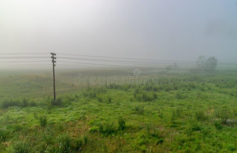Pilar de la electricidad en un campo en niebla imagenes de archivo