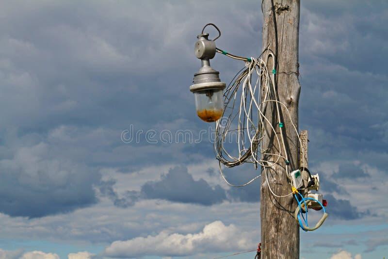 Pilar de madera con la linterna y los alambres viejos contra el cielo imagenes de archivo