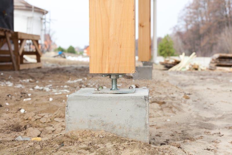 Pilar de madera en el hormigón del emplazamiento de la obra con el tornillo Los pilares de madera son las estructuras que se pued fotografía de archivo