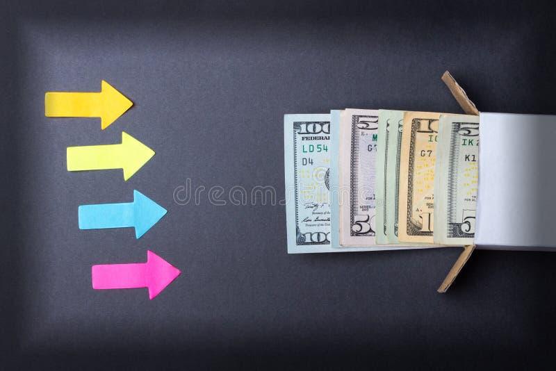 Pilar pekar till en bunt av dollarräkningar som ser ut ur asken Öka i besparingar Hem- kassaskåp äganderätt för home tangent för  royaltyfri foto