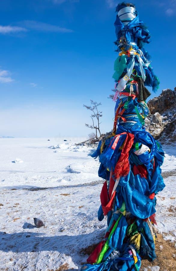 Pilar ritual de madera con las cintas coloridas en el cabo Burkhan fotografía de archivo