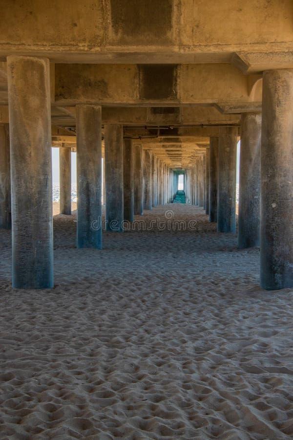 Pilares concretos por debajo un embarcadero largo en la playa imagenes de archivo