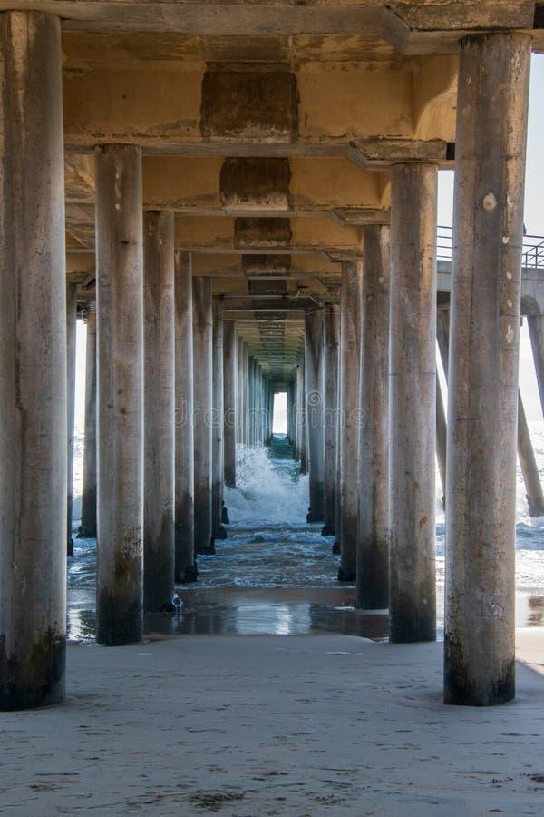 Pilares concretos por debajo un embarcadero largo en la playa fotos de archivo libres de regalías