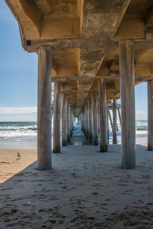 Pilares concretos por debajo un embarcadero largo en la playa fotografía de archivo