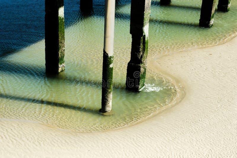 Pilares del embarcadero por marea baja imagen de archivo libre de regalías